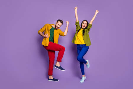 Full length body size view of his he her she nice attractive lucky cheery ecstatic couple dancing rejoicing rising hands up isolated bright vivid shine vibrant lilac violet purple color background