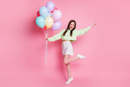 Full length photo of attractive lady arrange birthday party friend hold many air balloons meet guests wear casual green crop pullover jeans skirt shoes isolated pink pastel color background