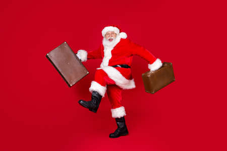 Full length photo of santa claus grey beard funny step hold vintage leather suitcase wear x-mas costume coat belt cap specs boots isolated red color background
