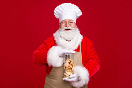 Photo of crazy white grey hair bearded santa claus hold ginger bread x-mas time eve cookies wear red costume apron isolated over bright shine color background