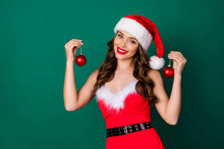 Photo of charming lady showing two newyear fir evergreen pine tree decor toys baubles offer sale price shopping sale discounts wear x-mas snow girl costume isolated green color background