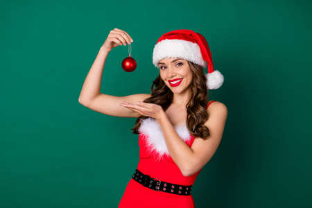 Photo of attractive cheerful lady hold newyear christmas tree decor red toy ball offer sale magic price sale holly atmosphere wear x-mas snow girl costume isolated green color background