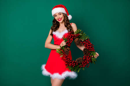 Photo of attractive cheerful lady hold newyear circle cone pine wreath christmas tree house entrance door decor holly atmosphere wear x-mas snow girl costume isolated green color background