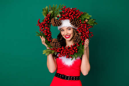 Photo of attractive cheerful lady look through newyear season circle cone wreath christmas tree house entrance door decor tradition wear snow girl costume isolated green color background