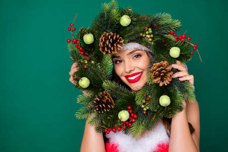 Photo of attractive lady look through newyear season circle wreath christmas tree door house entrance decor tradition good mood wear x-mas snow girl costume isolated green color background