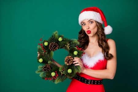 Photo of attractive lady hold newyear season circle wreath christmas tree door house entrance decor tradition send kiss wear x-mas snow girl dress santa cap isolated green color background