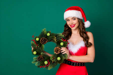 Photo of attractive cute lady hold arms newyear season green circle christmas tree door house entrance decor tradition wear x-mas snow girl dress santa cap isolated green color background