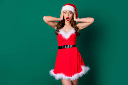 Photo of beautiful lady hold arms head open mouth not believe eyes shopper see sales discounts shopping newyear season wear x-mas snow girl dress santa cap isolated green color background