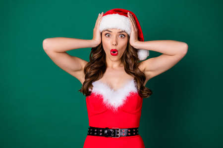 Photo of beautiful lady hold arms head open mouth shocked speechless expression see big sales discounts shopping center newyear wear x-mas costume santa cap isolated green color background
