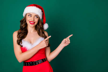 Photo of beautiful funny lady direct index fingers side empty space demonstrating novelty newyear sale prices poster wear red snow girl dress santa cap isolated green color background