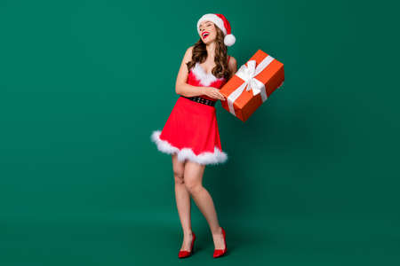 Full body photo of pretty funky snow girl lady newyear party friends house place hold big giftbox listen jokes lol wear mini red dress santa headwear stilettos isolated green color background