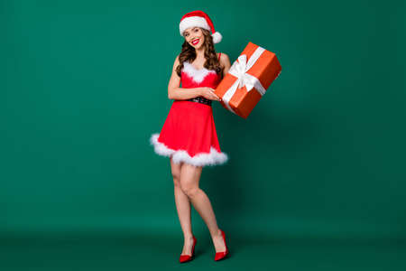 Full length photo of pretty snow girl role lady came newyear party friends house place hold large giftbox hands wear mini red dress santa headwear stilettos isolated green color background