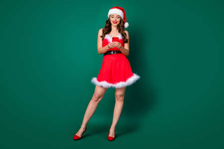 Full length photo of attractive santa assistant lady hold telephone read email online orders presents delivery service wear mini red dress x-mas cap costume isolated green color background