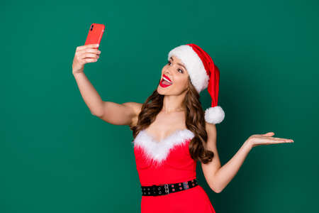 Photo of attractive santa secretary hold telephone receive customer video call order presents delivery service showing arm palm products wear x-mas costume isolated green color background