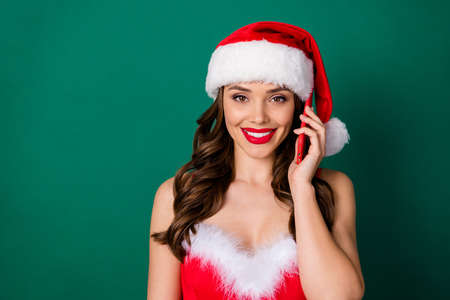 Photo of attractive charming santa assistant lady hold telephone receive call order presents delivery service wear red snow girl fluffy dress x-mas cap isolated green color background