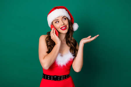 Photo of attractive santa assistant lady hold telephone receive call order presents delivery service say customer pricelist wear red snow girl dress x-mas cap isolated green color background