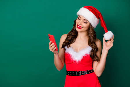 Portrait of her she nice attractive lovely focused cheerful cheery wavy-haired lady wearing Santa costume red lips using cell touching hat ball smm 5g app isolated green color background