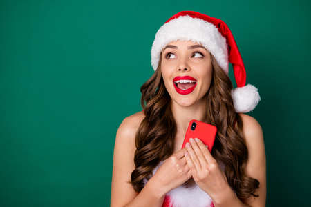 Close-up portrait of her she nice attractive lovely dreamy glad cheerful cheery wavy-haired lady wearing Santa look red lips using cell fantasizing sale discount isolated green color background