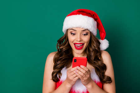 Close-up portrait of her she nice attractive stunning cheerful cheery focused amazed wavy-haired lady wearing Santa look red lips using cell app 5g sale discount isolated green color background