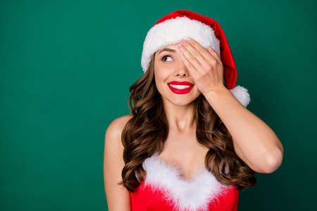 Close-up portrait of her she nice-looking attractive gorgeous cheerful cheery creative wavy-haired lady wearing Santa look closing one eye fantasizing red lips isolated over green color background