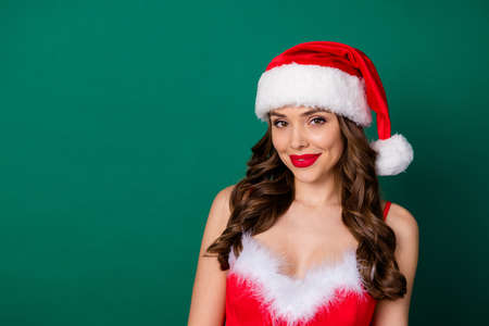 Portrait of pretty fancy lovely girl in santa claus cap look good mood enjoy x-mas jolly holly newyear event wear skirt dress isolated over green color background 版權商用圖片