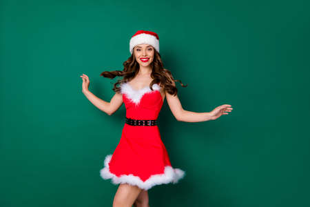 Photo of pretty lovely magnificent lovely girl in santa claus hat enjoy x-mas jolly holly celebration event wear chic belt skirt isolated over green color background