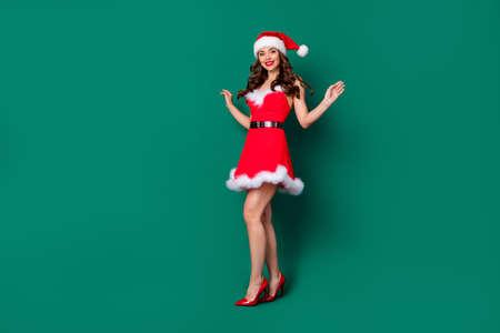 Full size photo of pretty lovely dreamy cute girl in santa claus headwear enjoy x-mas holly jolly newyear event wear skirt legs high-heels stilettos isolated green color background