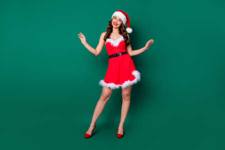 Full length photo of charming lovely gorgeous girl in santa claus headwear look good enjoy x-mas magic miracle dream newyear event wear legs high-heels isolated over green color