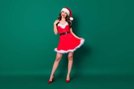 Full size photo of pretty charming sweet girl in santa claus headwear look good on x-mas magic miracle newyear event wear legs high-heels isolated over green color background 版權商用圖片