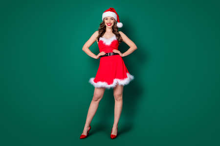 Full length photo of cute sweet magnificent girl in santa claus hat enjoy x-mas jolly holly magic event wear legs skirt high-heels isolated over green color background