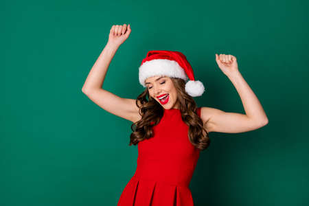 Photo of pretty sweet lovely girl in santa claus headwear enjoy dance x-mas fairy magic newyear party wear bright shine skirt isolated over green color background