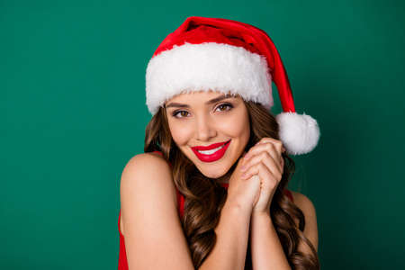 Close up photo sweet cute pretty lovely girl in santa claus headwear admire adore wish dream x-mas newyear present put hands together wear good look outfit isolated green color background