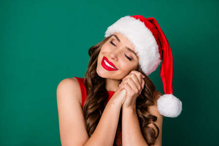 Close up photo of sweet lovely girl in santa claus headwear adore admire x-mas newyear present dream desire surprise wear good look outfit isolated over green color background