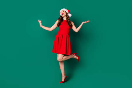 Full body photo of positive cheerful sweet magnificent lovely girl in santa claus headwear enjoy rejoice x-mas jolly holly event wear legs stilettos isolated green color background