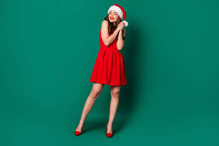 Full length photo pretty lovely sweet stunning girl inspired x-mas gift present surprise wish ask beg santa claus put hands wear skirt headwear high-heels isolated green color background