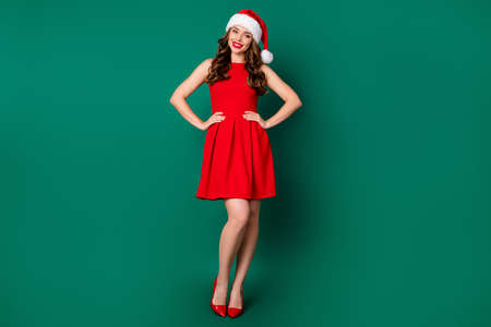 Full length photo of pretty sweet gorgeous santa claus girl enjoy x-mas fairy jolly event out hands waist wear bright shine high-heels stilettos look isolated green color background 版權商用圖片