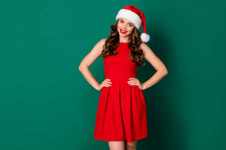 Photo of sweet gorgeous lovely girl in santa claus headwear enjoy advent jolly holly magic noel celebration put hands waist wear bright shine dress isolated over green color background 版權商用圖片