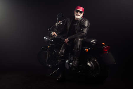 Full length photo of old cool man biker sit chopper engine enjoy fast speed route vacation trip wear bandanna boots isolated over black color background