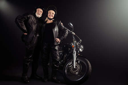Full length photo of old cool woman man biker couple hug embrace ready ride drive chopper freedom extreme adventure wear leather jacket vintage boots isolated black color background