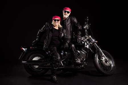 Photo of aged bikers grey haired man lady soulmates couple sitting on vintage chopper feel young going rock festival wear rocker leather jacket pants bandana isolated black color background