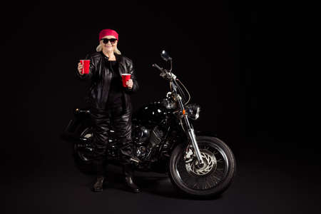 Full length body size view of her she nice attractive cheery grey-haired lady hipster rocker chopper rider wearing leather clothes inviting you drink beer party leisure isolated black color background
