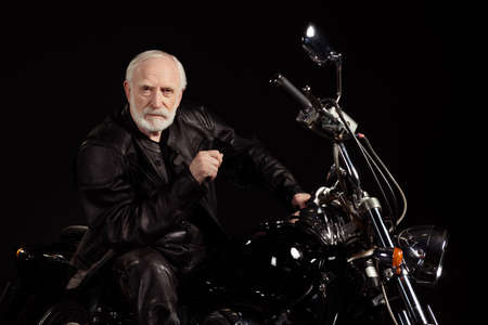 Portrait of his he nice old serious grey-haired dude hipster rocker punk traveler sitting on chopper spending time leisure hobby tour trip life insurance isolated black color background