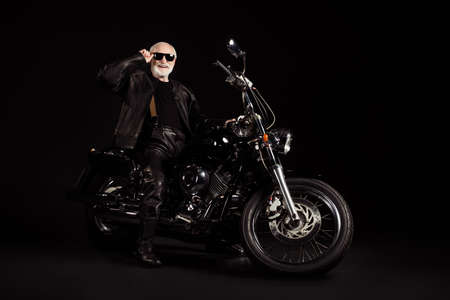 Portrait of his he nice attractive content cheerful grey-haired guy dude hipster traveler sitting on chopper spending weekend holiday tour trip touching specs isolated black color background
