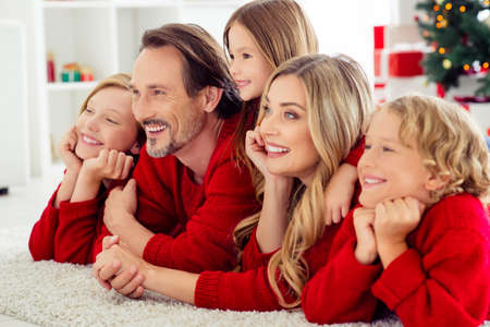 Close-up portrait of five nice attractive adorable careful cheerful family embracing spending festal day vacation watching movie tv film lying on floor in light white apartment indoor