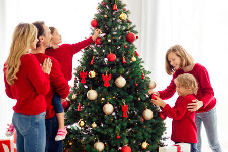 Portrait of nice adorable attractive big full cheerful family small little kids embracing spending time decorating tree festive day custom in light white apartment house indoor