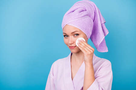Photo of charming woman hand hold white sponge cheekbone wear violet towel turban bath robe isolated blue color background Stock Photo