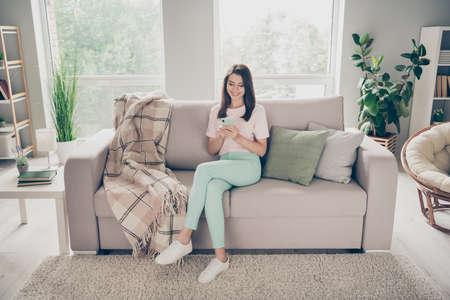 Photo portrait of modest woman sitting on couch with crossed legs holding phone in two hands indoors