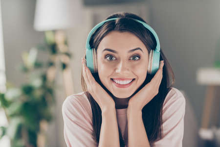 Close-up portrait of her she nice attractive pretty charming glad cheerful dreamy brown-haired girl fan wearing blue headset listening radio chart staying home apartment Stock fotó
