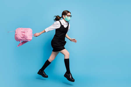 Full length profile side photo of high school girl jump run fast lecture hold rucksack backpack wear white blouse black skirt dress long socks overall isolated blue color background