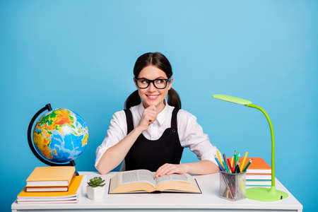 Photo minded girl university student sit table read textbook think thoughts touch hand chin look copyspace wear white blouse black overall ponytails uniform isolated blue color background